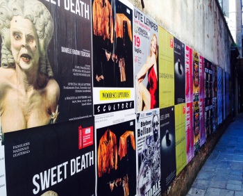 Street wall in Venice filled with posters on theater and film works.